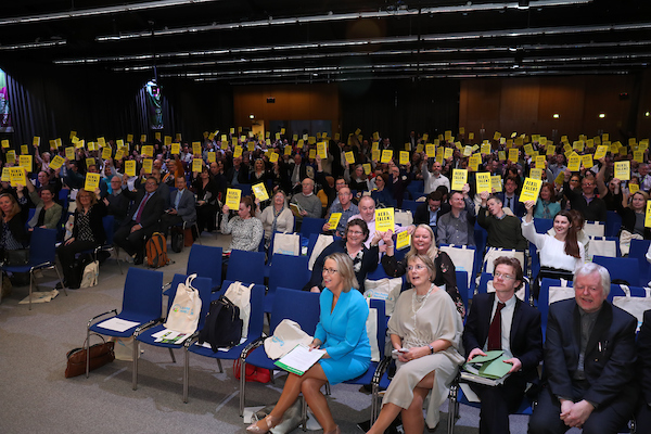 Everyone in the audience at the Innovation Conference holding up the 'Rebel Talent' book
