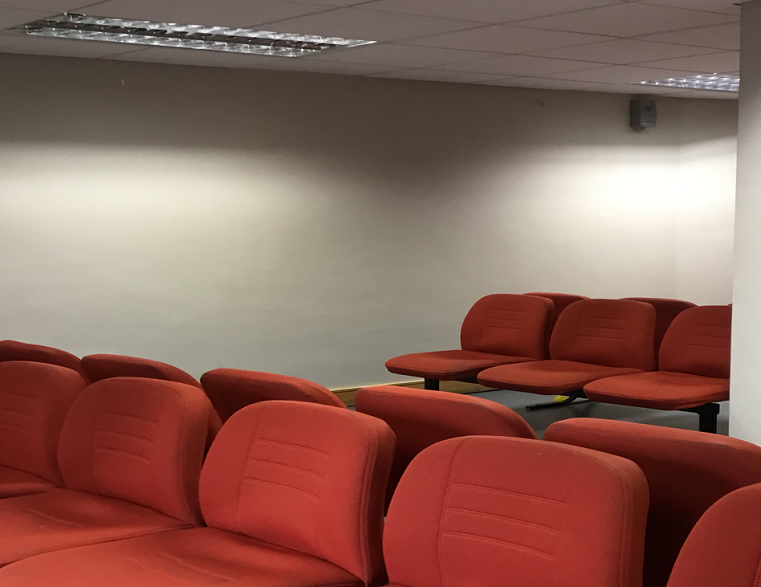 Courts service waiting area with a blank wall