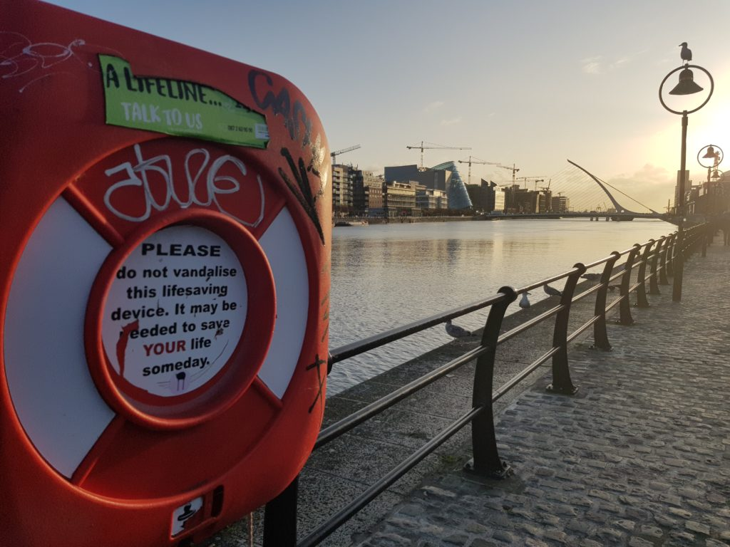 A ring buoy at Dublin Docklands with Samuel Beckett bridge in the background.
