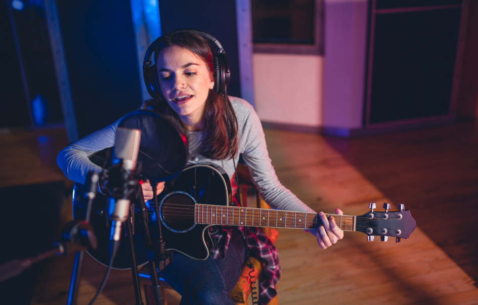 Teenager playing guitar and singing in a studio