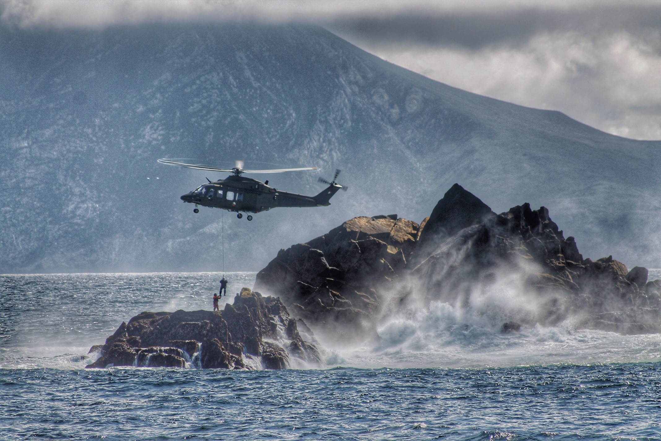 Helicopter winching by Defence Forces at an island off the coast